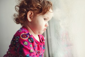 Sad little girl looking out the window.